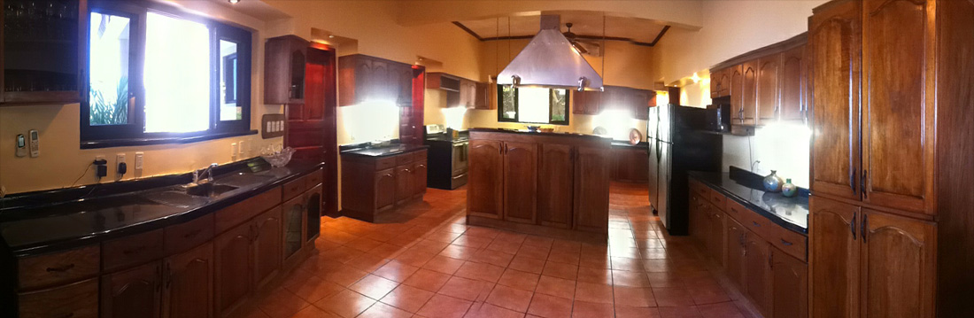 Large kitchen with two different spaces, one for cooking and another for bartender.